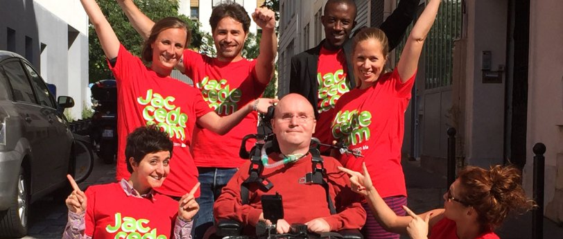 group photo of people in red with arms raised in the air looking happy , man in wheelchair sitting in front smiling.
