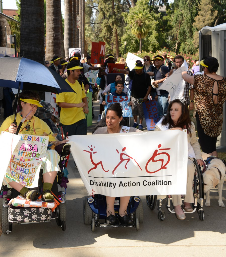 3 women all chair users leading the March at the capitol holding the Disability Action Coalition banner