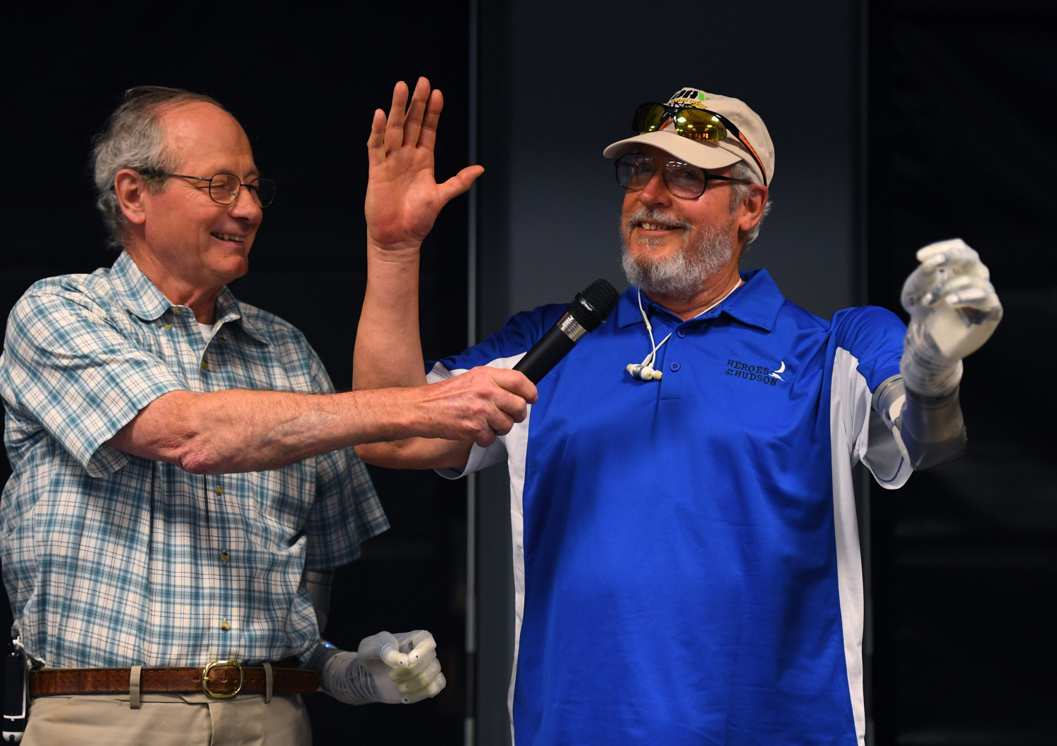 US Army veteran Fred Downs smiles as US Army Veteran Artie McAuley(R) is shown with his LUKE prosthetic arm, during a live demonstration of the first veteran being fitted with LUKE (Life Under Kinetic Evolution) prosthetic arm.