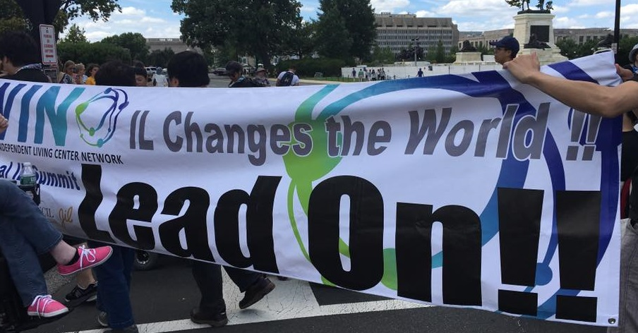 "People holding a banner saying ""IL changes the world, Lead on"""