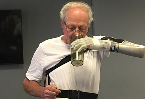 Vietnam Veteran Fred Downs using the prosthetic arm to drink a glass of water