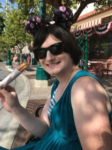 Women sitting on a bench at Disneyland park smiling and eating a churro while wearing dark sunglasses
