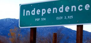 "Green Road sign that reads ""Independence, Pop. 574, Elev 3,925"