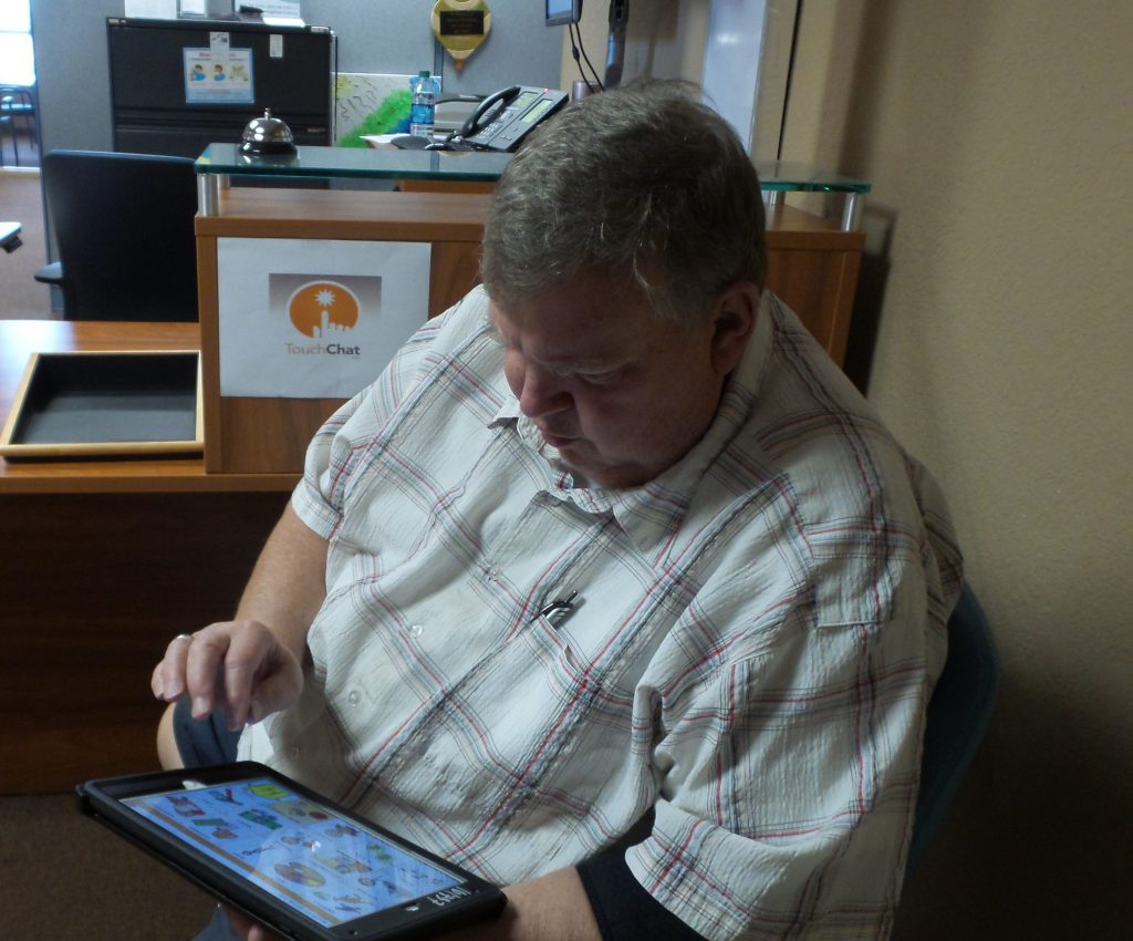 older gentleman sitting in an office trying out an ipad with the touchchat app on it