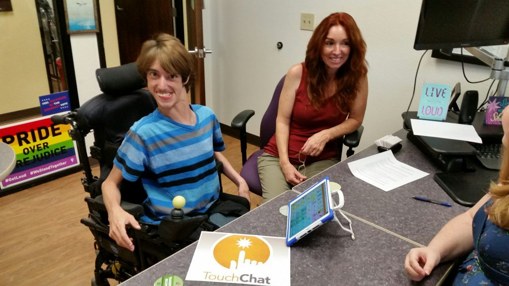 A young man using a power chair is sitting next to his mom in an office. There is an iPad on the table with a speech app.