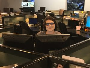 Women smiling and wearing slightly shaded glasses while sitting at her computer screens within a cubicle