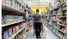 women and service dog walking down the aisle in a grocery store