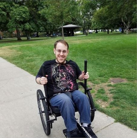 Man sits in modified manual chair smiling with his hands on the push handles propelling him forward