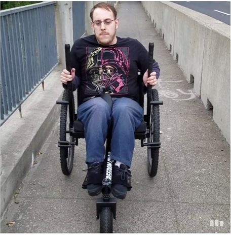 Man sitting in modified chair pushing the large handles that propel him forward