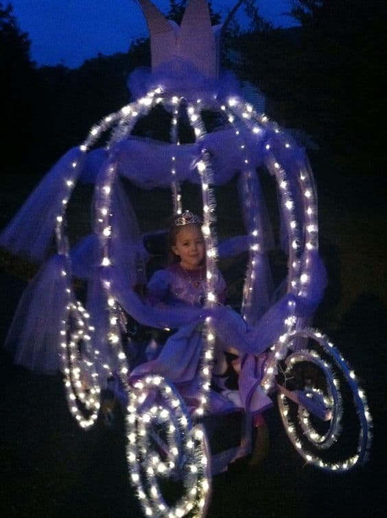 Little girl dressed in a beautiful pink princess dress sits in her power chair decorated to look like a big carriage equipped with twinkling lights and Tull