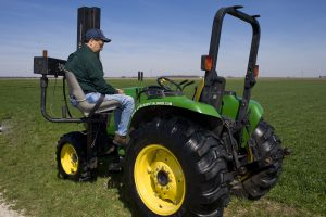 Man using a motorized transfer/lift chair to lift him into the tractor seat