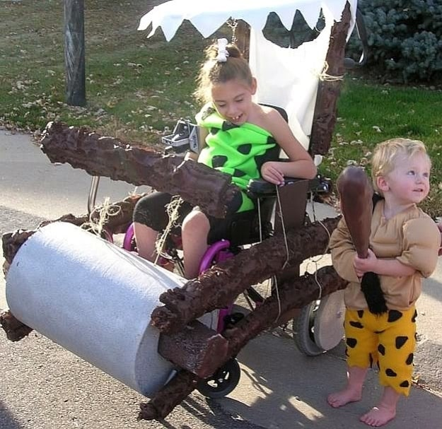 little girl dressed in green cave women outfit with a bone in her ponytail. Her power chair is decorated to look like a prehistoric car like the ones featured in the Flintstones