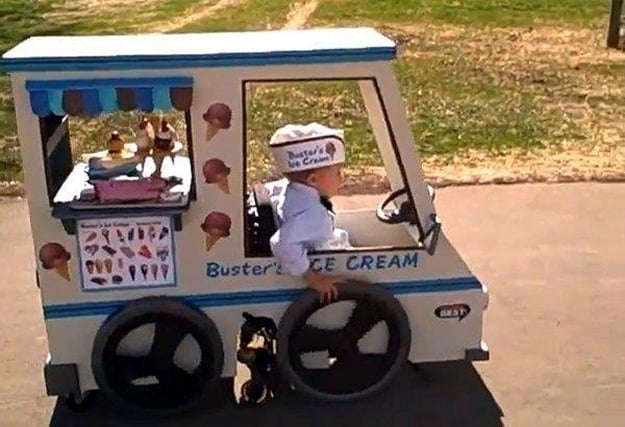 "Little boy wears a white hat that reads ""busters ice cream"" along with a bow tie. The little boy pushes his manual chair that is designed to look like an ice cream truck stocked with faux ice cream cones in the back window"
