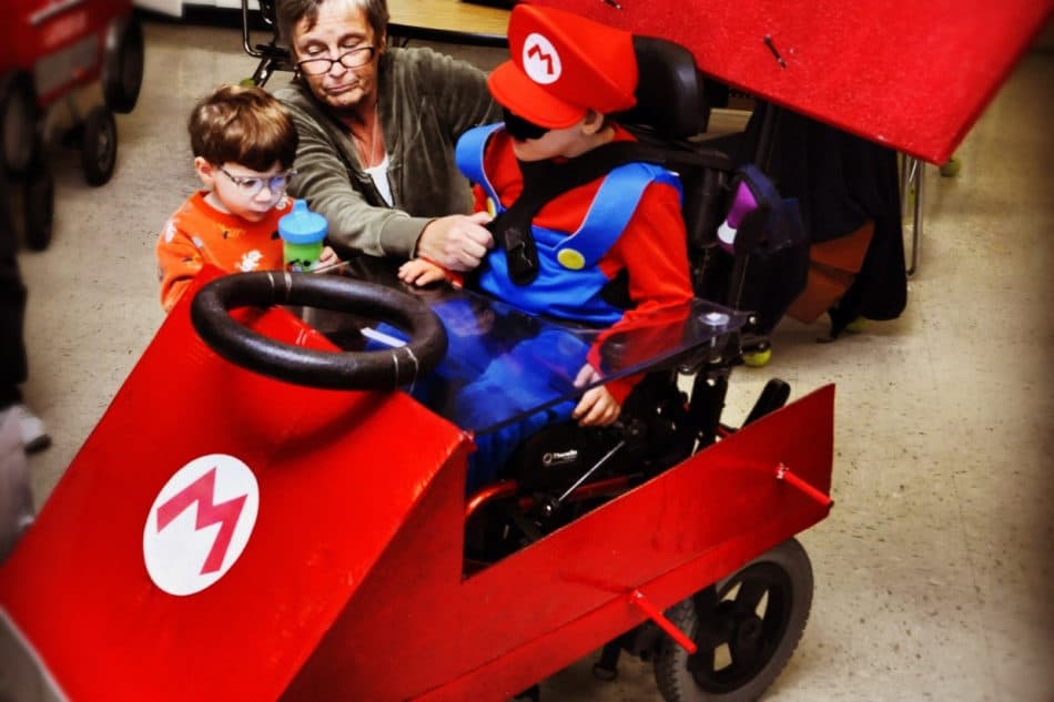 Little boy dressed in blue overalls and a red hat and mustache dressed to look like Mario, sits in his power chair decorated to look like a Red go Kart