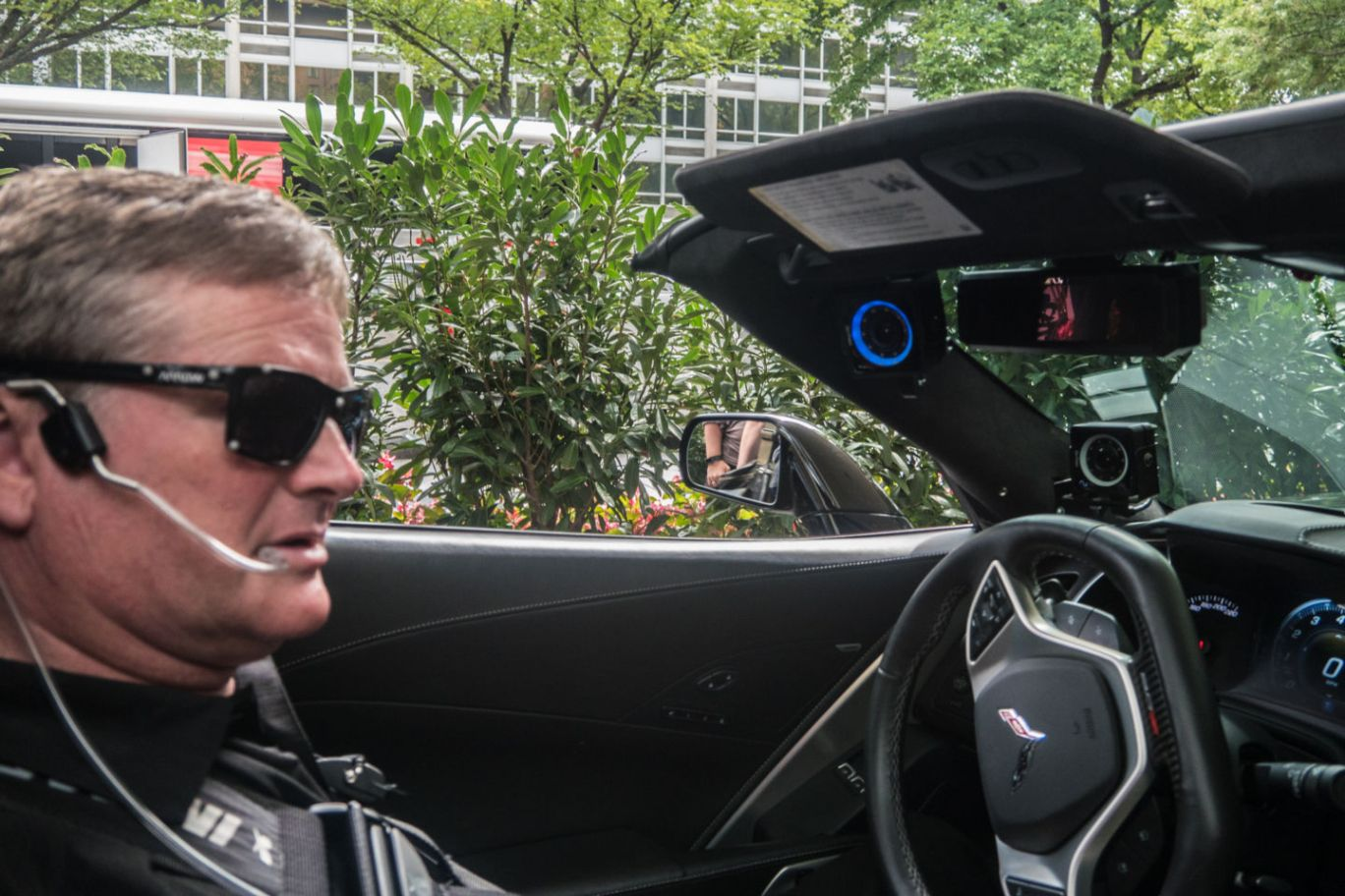 Sam Schmidt sits in driver seat of his convertible corvette wearing specialized sunglasses and a headset that control his vehicle