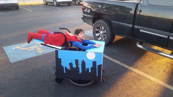 Little boy dressed as super man along with a fake torso off the back of his wheelchair that gives the illusion he is flying over the city scape