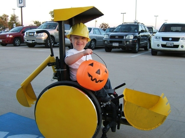 Little boy wearing a hard hat and holding up a jack-o-lantern pale while he sits in his power chair that is decorated to look like a little yellow bulldozer