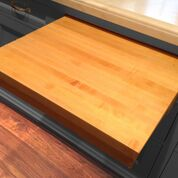 built- in light wood colored cutting board sliding out of the kitchen counter