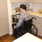 A man using a wheelchair is heating up a meal in the microwave. The microwave is a pull out drawer that is below the countertop.