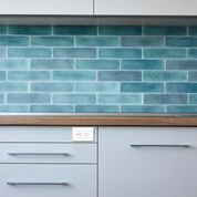 There is a cabinet with a bright teal back splash, there is an electrical outlet embedded above the cabinet drawers.