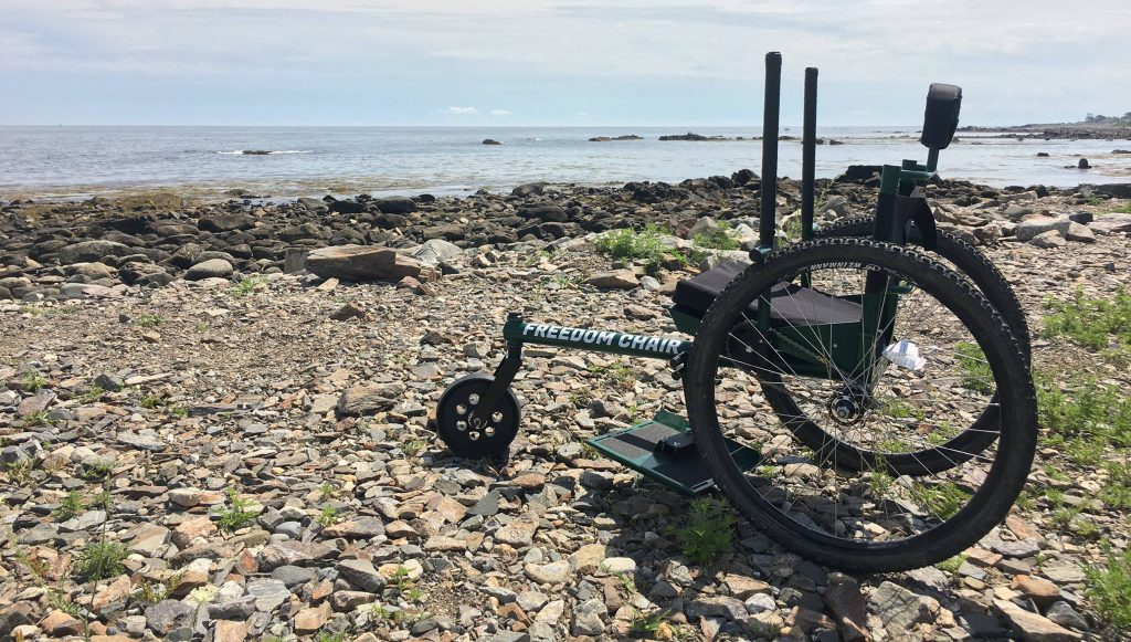 Side view of the green GRIT Freedom Chair sitting on a rocky beach