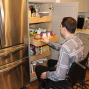 man sitting in manual chair in front of a pantry with pull out shelves