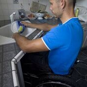 A gentleman using a wheelchair is pulled up at his roll under sink washing a plate.