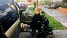 A woman is riding her power wheelchair up the ramp of her accessible van.