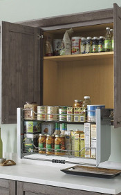 There is a pull down shelf in the pantry with spices and oils on it.