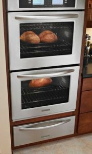 There are two stacked wall ovens with bread baking inside.