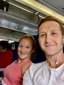 A woman wearing a pink top and a man wearing earbud headphones are sitting together on an airplane.