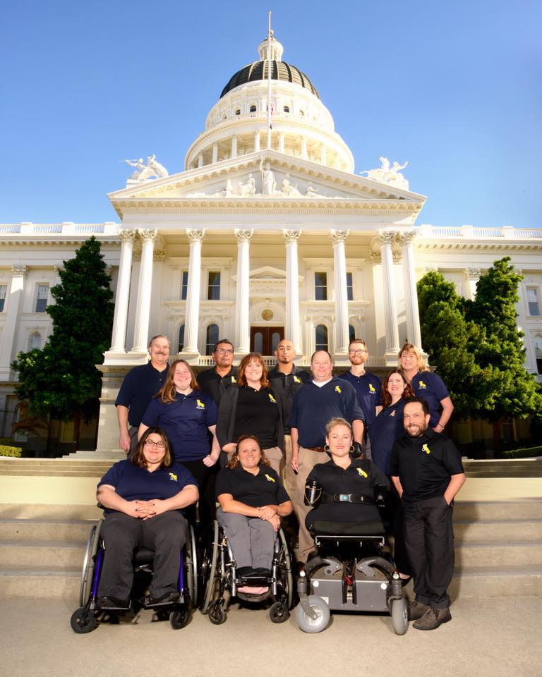 A group of 13 people wearing CFILC shirts are in front of the California Capitol Building.
