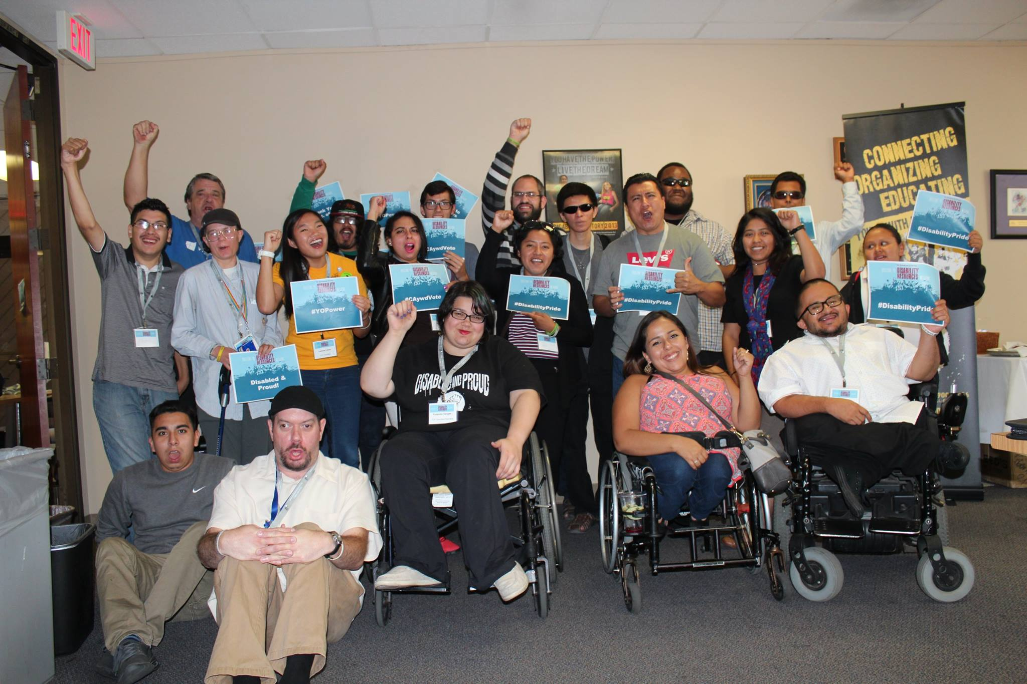 A group of people with disabilities are together with their hands up in a fist.