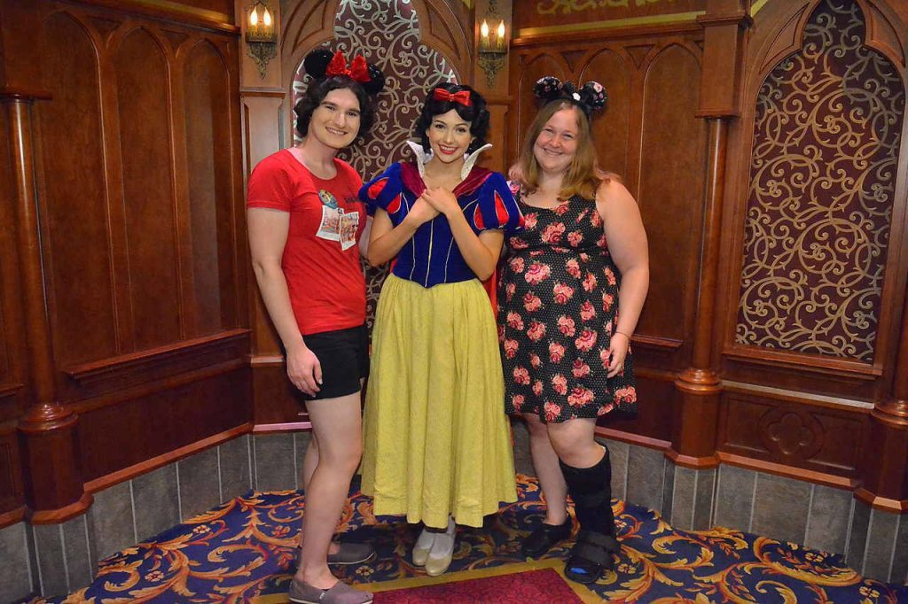 A photo of three women, one is dressed as Snow White and the others are wearing Mouse ears. One of the women is wearing a walking boot.