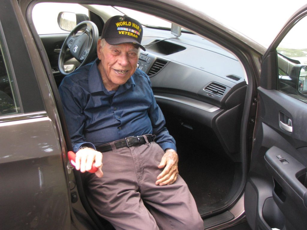 A senior male wearing a Vietnam Veterans hat is using the handy bar to help get out of the car.