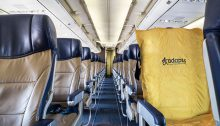 The photo is of the inside of an empty airplane. One of the seats has a yellow ADAPTS sling covering it.