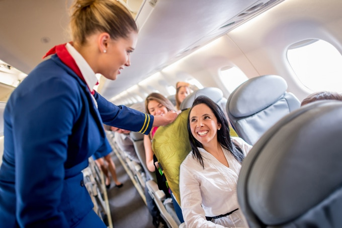 A woman is sitting on an airplane seat with the ADAPTS sling beneath her talking to a flight attendant.