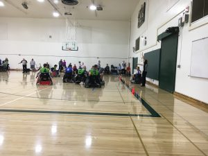 Two Rugby Wheelchair teams, one wearing blue the other green, are playing on a basketball court.