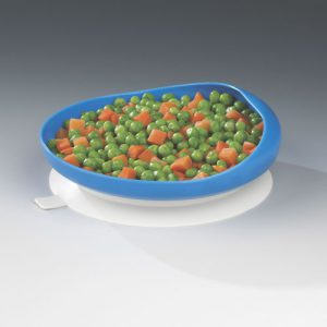 A photo of a plate suctioned to a table. It has a large blue rim holding peas and carrots.