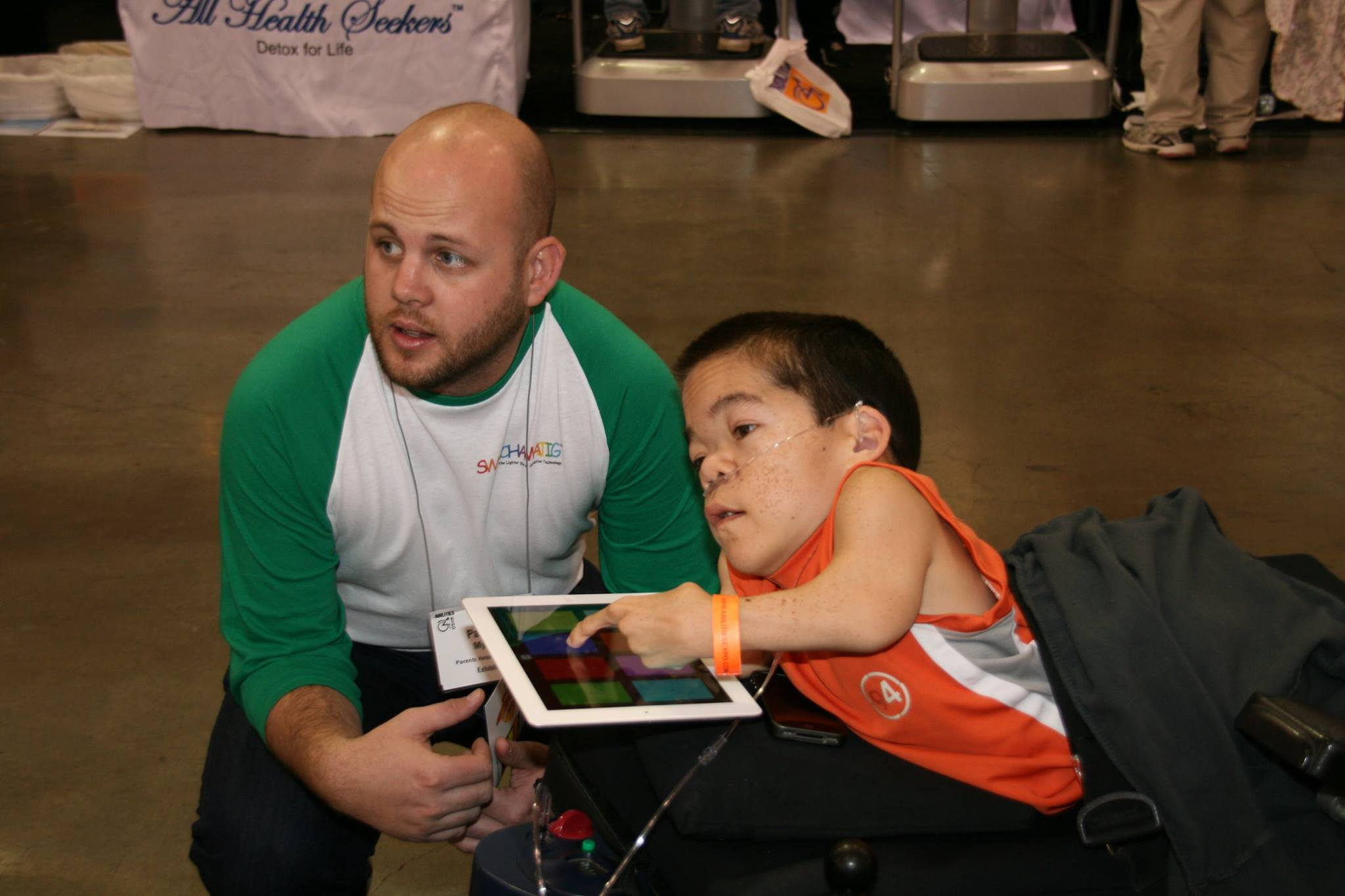A man wearing a baseball shirt is crouching down. He is next to a man using a wheelchair holding an iPad.