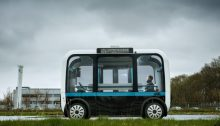 olli bus self drives through a campus with people sitting inside