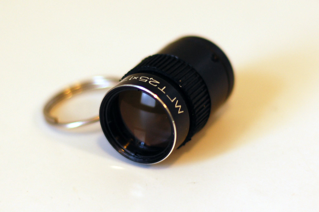 A small black monocular telescope. It looks like an adjustable camera lens and is on a silver keychain.