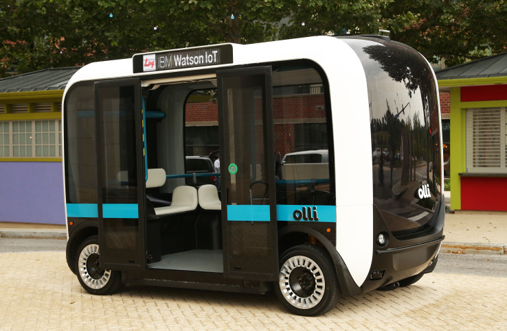 the black,white, and blue Olli bus sits in city scene with boors open welcoming passengers