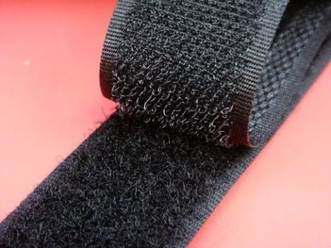There is a red background. A black roll of velcro partially unrolled lays on top.