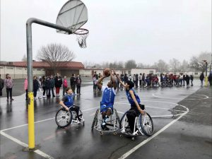 Two youth are playing wheelchair basketball outside. One is trying to make a shot.