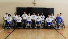 The Sacramento Royals Wheelchair Basketball team posing for a group photo in their white uniforms.