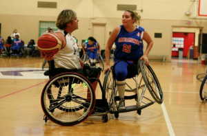Two women are playing wheelchair basketball. The one on the left has the ball, Alicia is on the right trying to block her.