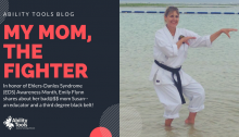 "The image is of a woman standing in ankle deep water. She is wearing a traditional white karate uniform with her black belt. She is in a karate pose. The text is on a dark blue background. It is white and red, it reads ""Ability Tools Blog My Mom, The Fighter. In honor of Ehlers-Danlos Syndrome (EDS) Awareness Month, Emily Flynn shares about her bad@ss mom Susan--an educator and a third degree black belt!"""