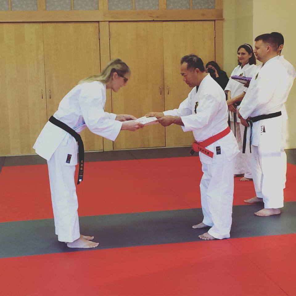 women in traditional martial arts uniform bowing towards man handing her a certificate