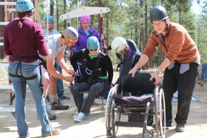 GCR staffers help a youth in wheelchair get ready for the ropes course.